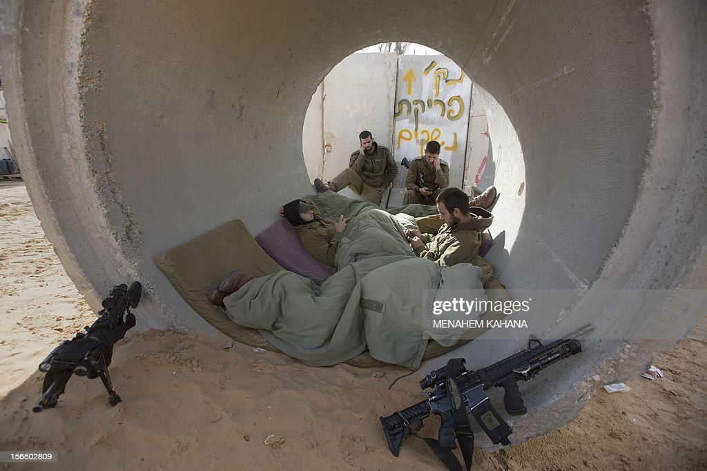 Israeli soldiers rest inside a large concrete pipe used a as shelter for  rockets fired by