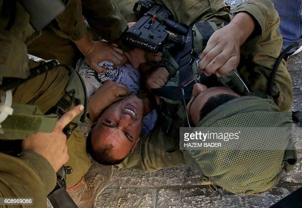 TOPSHOT Israeli soldiers restrain a Palestinian man as troops try to arrest him in the flashpoint city of Hebron in the Israelioccupied West Bank on...