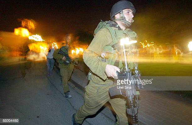 Israeli soldiers run for positions during exchanges of fire in the Jewish Gaza Strip settlement of Morag July 6 2005 in the Gush Katif settlements...