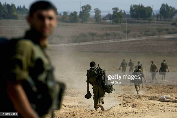 Israeli soldiers seen as they break action for a rest on the Israeli side of the Green Line near the Gaza Strip town of Beit Hanun October 3 2004 in...