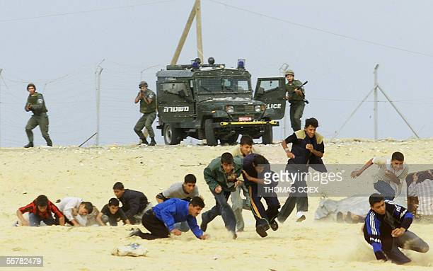 Israeli soldiers shoot at stonethrowing Palestinian teenagers in Khan Yunes in the Gaza Strip during clashes 24 October 2000 Exhausted by a conflict...