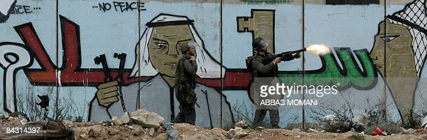 Israeli soldiers shoot tear gas at Palestinian youths during clashes that followed a protest against Israel�s offensive in the Gaza Strip at Qalandia...
