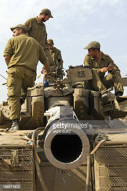 Israeli soldiers sit atop a tank on the Israeli side of the border with the Gaza Strip on November 17 2012 Israeli air strikes destroyed the cabinet...