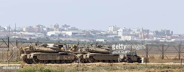 Israeli soldiers sit atop their tanks on the Israeli side of the border with the Gaza Strip on July 3 2014 Israeli warplanes pounded Gaza and...