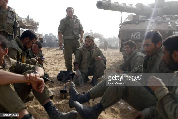Israeli soldiers sit next to a tank in a deployment area on August 02 2014 on Israel's border with the Gaza Strip The Israeli military on Friday...