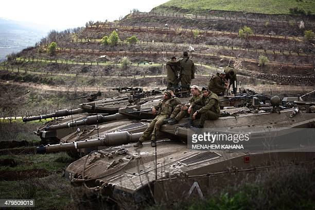 Israeli soldiers sit on their Merkava tanks after being deployed on the border with Syria near the Druze village of Majdal Shams on March 19, 2014 in...