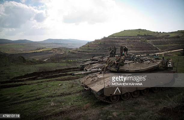 Israeli soldiers sit on their Merkava tanks after being deployed on the border with Syria near the Druze village of Majdal Shams on March 19 2014 in...