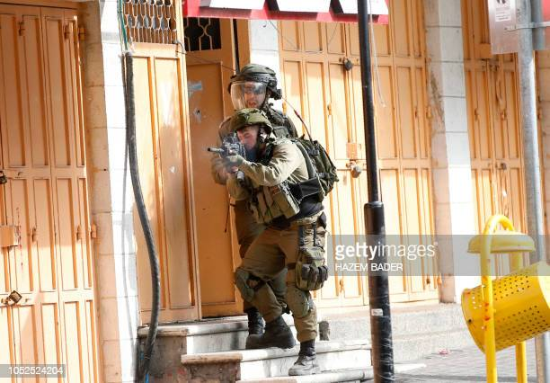 Israeli soldiers stand and take aim next to a shop's open door along a street during clashes with Palestinian protesters following a demonstration...