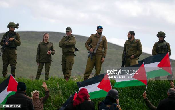 Israeli soldiers stand at attention as Palestinian demonstrators take part in a protest against the annexation of the Jordan Valley in the village of...