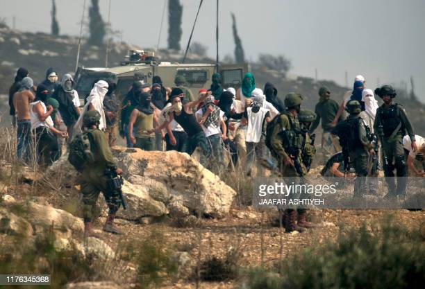 Israeli soldiers stand by as masked Israeli settlers throw stones at Palestinian protesters gathering during a demonstration against construction on...