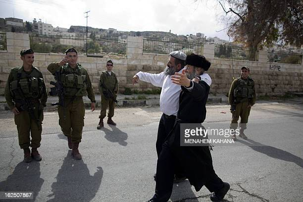 Israeli soldiers stand guard as Jewish settlers celebrate the annual Purim parade on February 24 2013 in the occupied West Bank city of Hebron Purim...