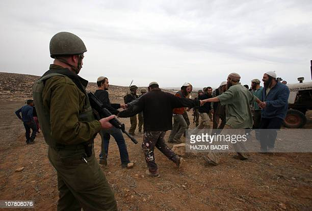 Israeli soldiers stand guard as Jewish settlers from the nearby Matsbe Yair settlement sing and dance on a Palestinian land after they tried to...