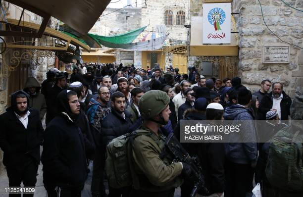 Israeli soldiers stand guard as Jewish settlers tour the Palestinian side of the old city market in the divided West Bank city of Hebron on February...