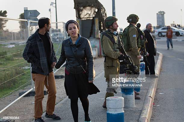 Israeli soldiers stand guard next to Israeli commuters at a bus station where a Palestinian attacker stabbed an Israeli woman before being shot dead...