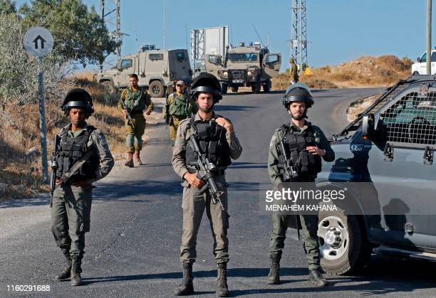 Israeli soldiers stand guard next to the site where the body of an Israeli soldier was found with multiple stabs near the settlement of Migdal Oz in...