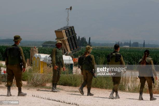 Israeli soldiers stand in front of an Iron Dome defence system battery, designed to intercept and destroy incoming short-range rockets and artillery...