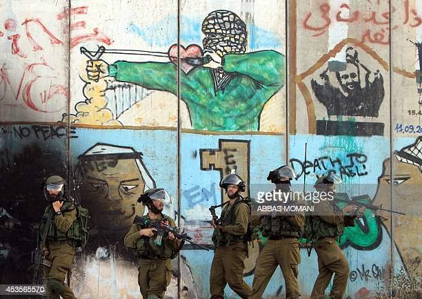 Israeli soldiers stand in front of the graffiti covered controversial separationbarrier during clashes with Palestinian stone throwers who rallied to...