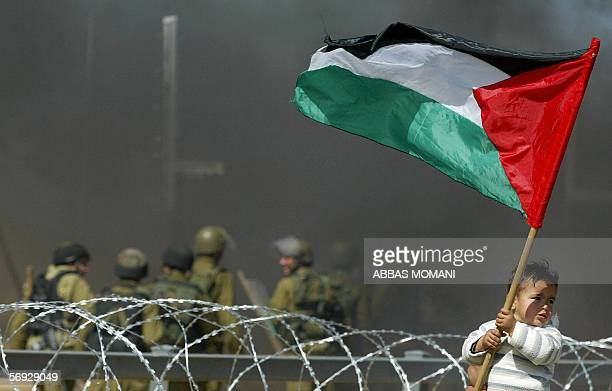 Israeli soldiers stand in the distant as a Palestinian child holds up the national flag during a protest against the controversial Israeli separation...
