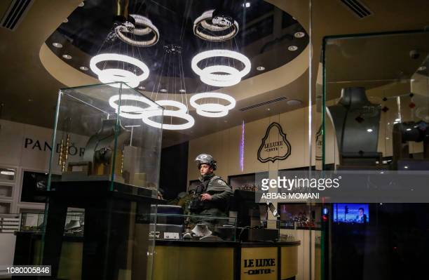 Israeli soldiers stand inside a jewellery shop during a security raid in the West Bank city of Ramallah on January 10 after shooting on an Israeli...