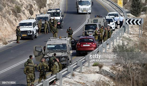 Israeli soldiers stand next to a car from which a Palestinian reportedly exited and stabbed an Israeli soldier before being shot dead on August 24...
