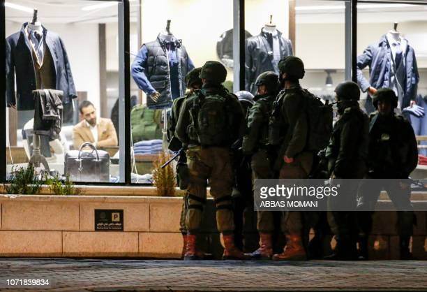 Israeli soldiers stand next to a Palestinian retail clothing shop in the occupied West Bank city of Ramallah on December 11 2018 Israeli forces in...