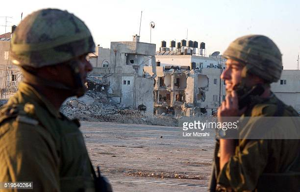 Israeli soldiers stand next to the damaged compound of Palestinian President Yasser Arafat in the West Bank city of Ramallah September 22 2002 The...