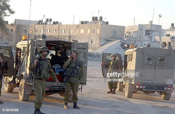 Israeli soldiers stand next to the damaged compound of Palestinian President Yasser Arafat in the West Bank city of Ramallah September 22, 2002. The...