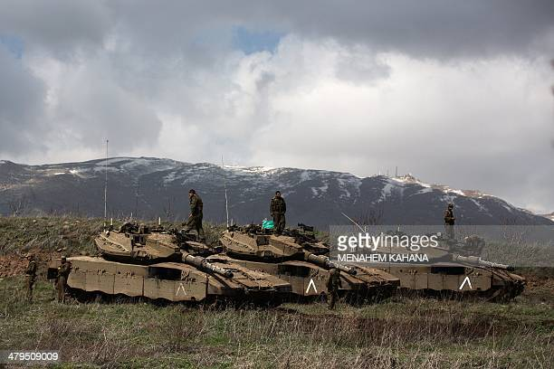 Israeli soldiers stand on alert on their Merkava tanks after being deployed on the border with Syria near the Druze village of Majdal Shams on March...