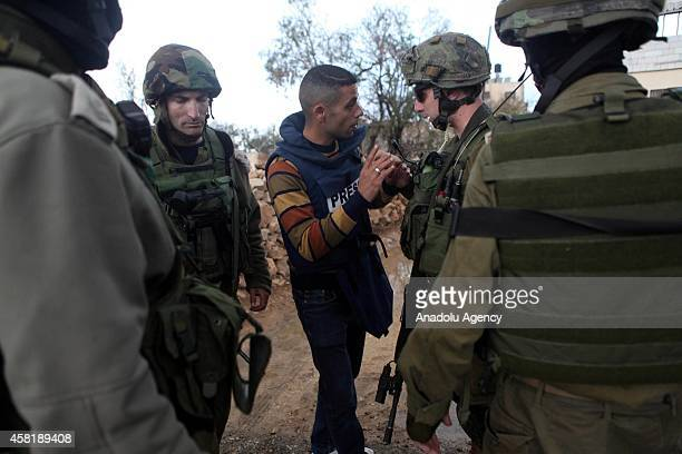 Israeli soldiers take a Palestinian press reporter under custody after Palestinians performed Friday Prayer due to Israeli Government's entrance...