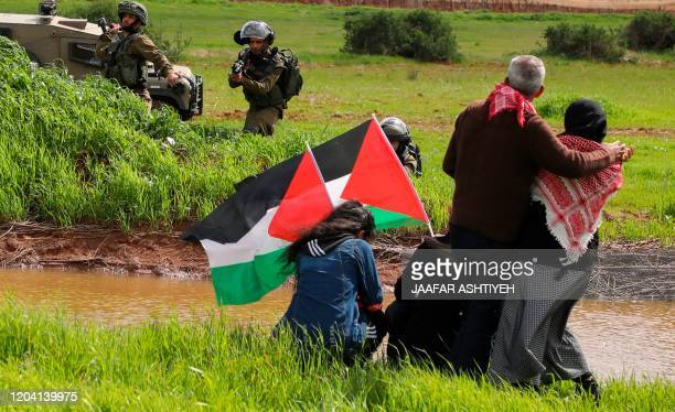TOPSHOT Israeli soldiers take aim as Palestinian demonstrators take part in a protest against the annexation of the Jordan Valley in the village of...