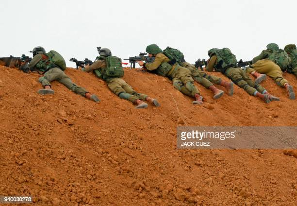 Israeli soldiers take aim as they lie prone over an earth barrier along the border with the Gaza strip in the southern Israeli kibbutz of Nahal Oz on...
