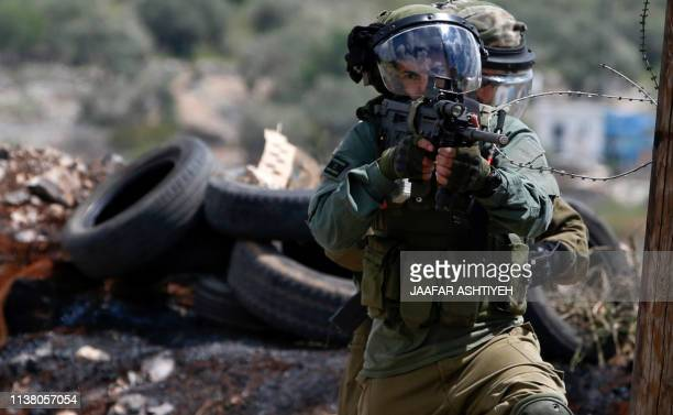 Israeli soldiers take aim at Palestinian protesters following a weekly demonstration against the expropriation of Palestinian lands in the village of...