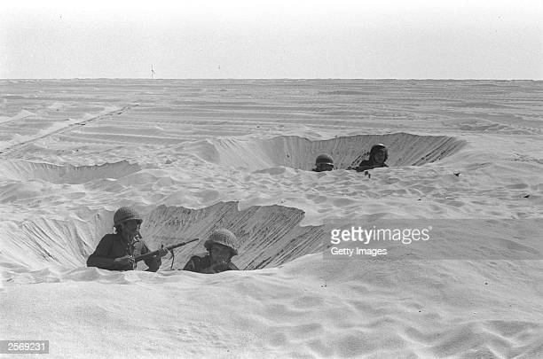 Israeli soldiers take cover in their foxholes during fighting against the Egyptians October 14 1973 in the Sinai Desert during the Yom Kippur War...