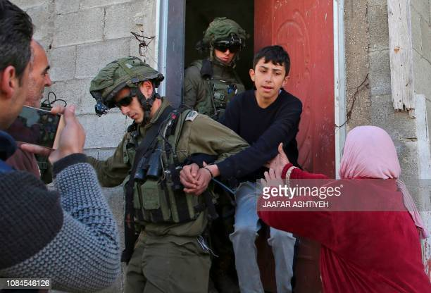 TOPSHOT Israeli soldiers take into custody a Palestinian youth as Palestinian women protest following a demonstration against the expropriation of...