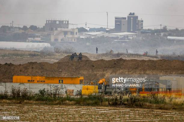 TOPSHOT Israeli soldiers take position along with border with the Gaza strip near the southern Israeli kibbutz of Nahal Oz on May 4 during clashes...
