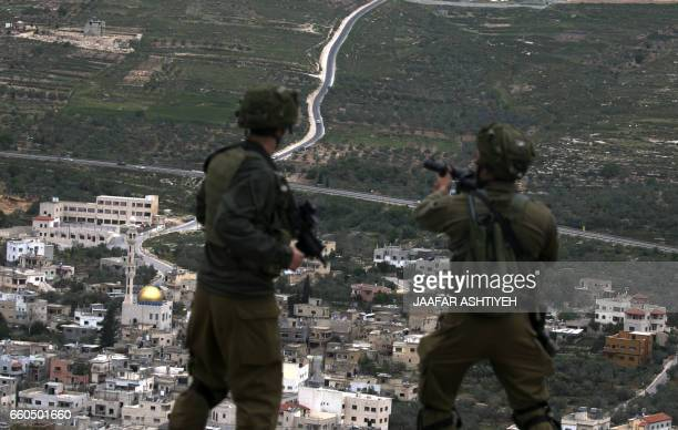 Israeli soldiers take position during a protest to mark land day in the West Bank village of Madama south of Nablus on March 30 2017 Land Day marks...