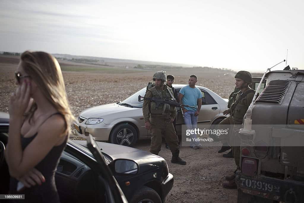 Israeli soldiers talk with civilians during a patrol next to the Israeli-Palestinian border as some 16,000 reserve troops are drafted in, on November 16, 2012 in Israel. Conflict between the Israeli military and Palestine militants has intensified over the last few days, with Israel striking some 130 targets overnight. According to reports, 18 Palestians and three Israelis have been killed. Egypt's prime minister Hisham Qandil is due to make a brief visit to Gaza today and Israel have vowed to suspend fire for the duration of his visit, provided there's no cross border attacks from militants.