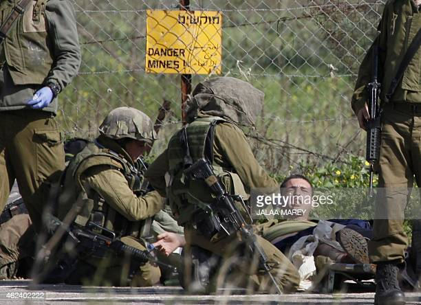 Israeli soldiers treat their injured comrades in the divided village of Ghajar after an antitank missile hit an army vehicle in the Israeloccupied...