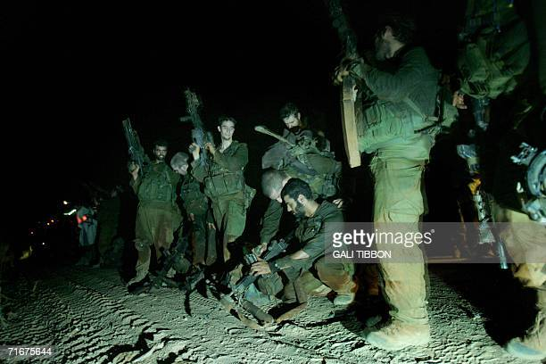 Israeli soldiers unload their weapons as they stand along the international border with Lebanon moments after they crossed back into Israel 19 August...