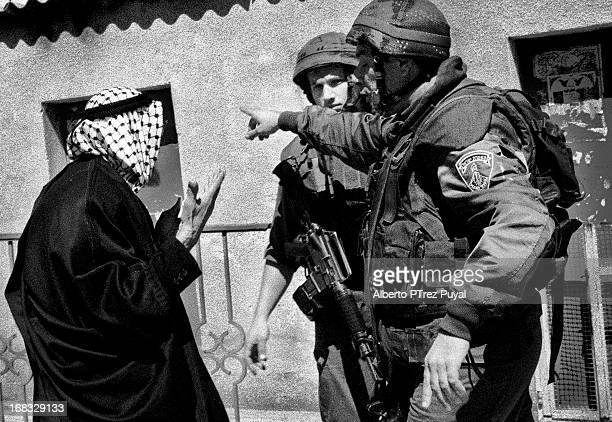 CONTENT] Israeli soldiers urge a palestinian to leave clashes area during second Intifada
