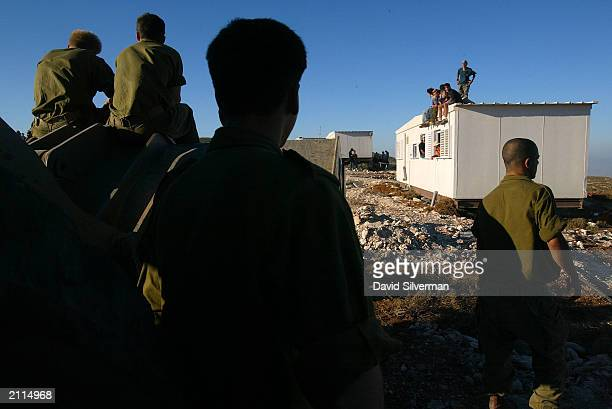 Israeli soldiers wait for orders to evacuate rightwing Jewish settlers who occupy a mobile home during an attempt to dismantle the illegal settlement...