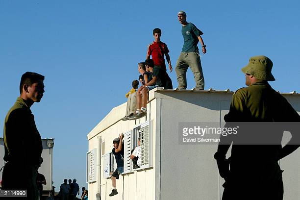 Israeli soldiers wait for orders to evacuate rightwing Jewish settlers who occupy a mobile home to thwart attempts by the army to dismantle the...
