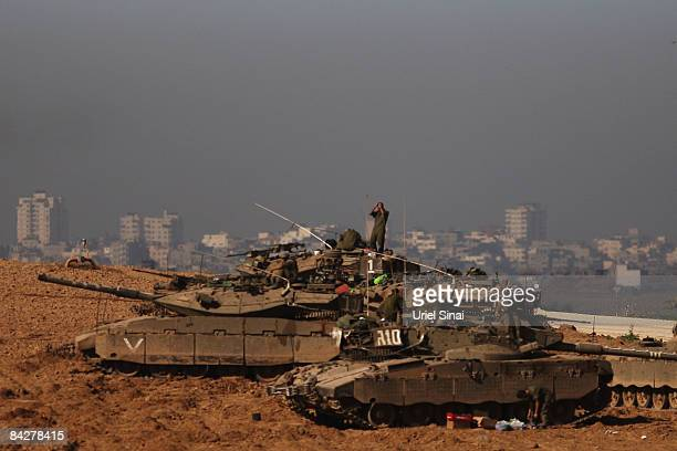 Israeli soldiers wait on top of their tanks at a staging area on January 14 2009 at the border with the Gaza Strip Israeli air strikes continued...