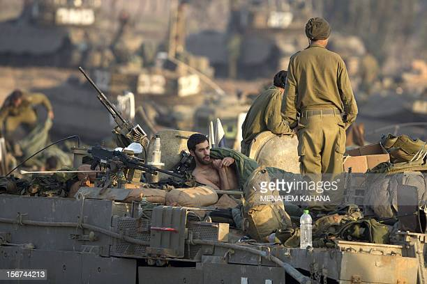 Israeli soldiers wake up after spending a night sleeping on top of their tanks at an Israeli army deployment area near the IsraelGaza Strip border on...