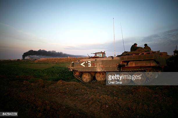 Israeli soldiers wake up on top of an APC as smoke rises from Gaza on January 15 2009 at the border with the Gaza Strip Israel forces attacked 70...