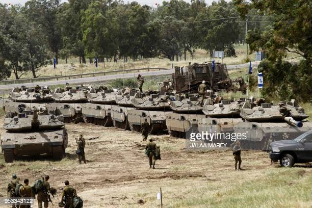 Israeli soldiers walk by Merkava Mark IV tanks during a military drill in the Israeliannexed Golan Heights on May 1 2018