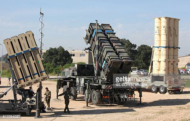 Israeli soldiers walk near an Israeli Irone Dome defence system a surfacetoair missile system the MIM104 Patriot and an antiballistic missile the...