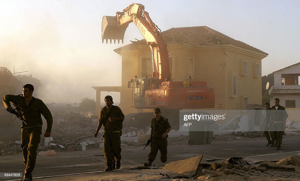 Israeli soldiers walk past a bulldozer d : News Photo