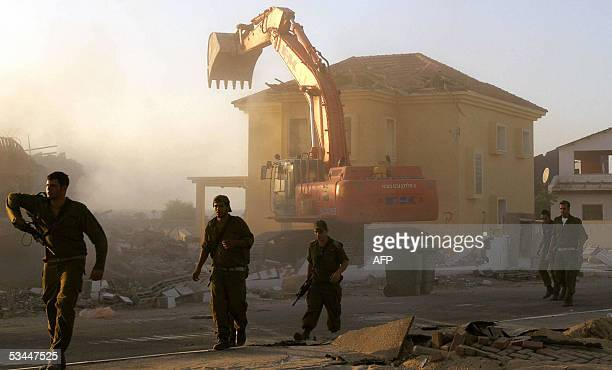 Israeli soldiers walk past a bulldozer demolishing a house in the Gaza Strip settlement of Peat Sade 21 August 2005 Israel's pullout from the Gaza...