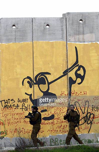 Israeli soldiers walk past a graffiti drawing of the late Mahatma Ghandi on Israel's security barrier during clashes with Palestinian demonstrators...